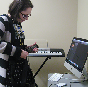 A patron playing a JamStik guitar next to a Mac computer with a digital keyboard in the background.